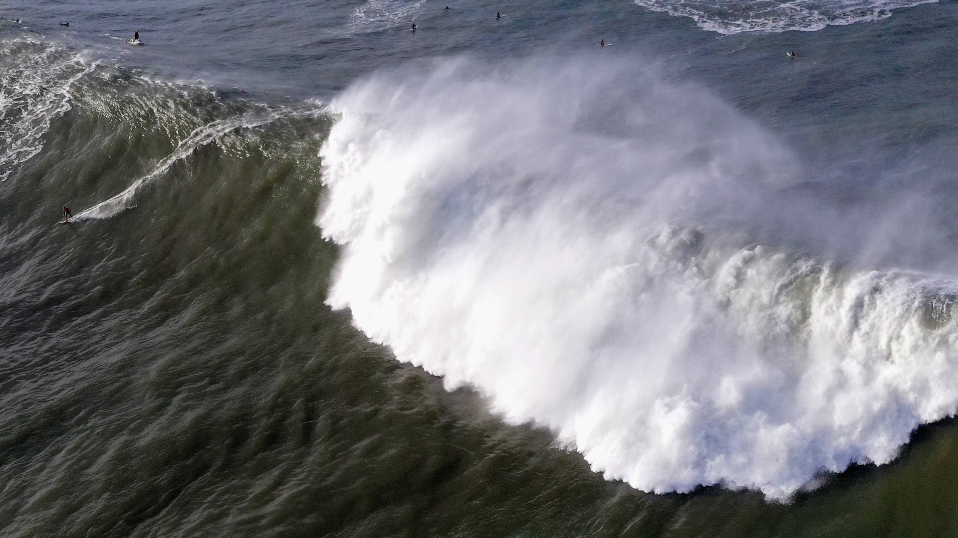 """A surfer rides a wave at Mavericks off Half Moon Bay on Monday. The NWS warned of waves that could reach """"50+ feet at favored breaks"""" in Northern California. Ezra Shaw/Getty Images"""