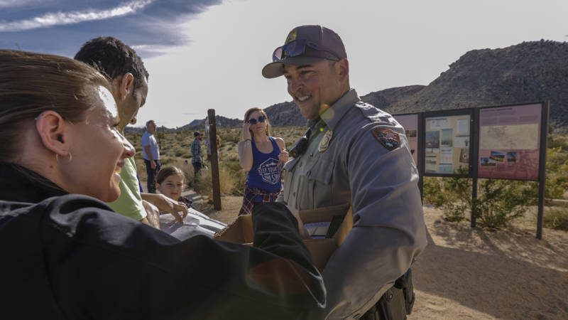 Lone park ranger Dylan Moe at the entrance to Joshua Tree National Park provides park maps to visitors on Saturday, December 22, 2018. The park was open but its visitors center and other facilities were closed due to the partial government shutdown.