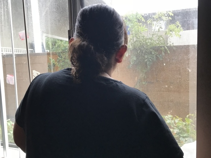 Lizeth, an immigrant from Honduras, looks out the window of her studio apartment in Los Angeles.