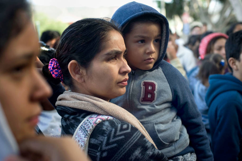 A woman and child wait to hear their position on a list of asylum-seekers waiting at the U.S.-Mexico border on Nov. 21, 2018.  David Maung/KQED