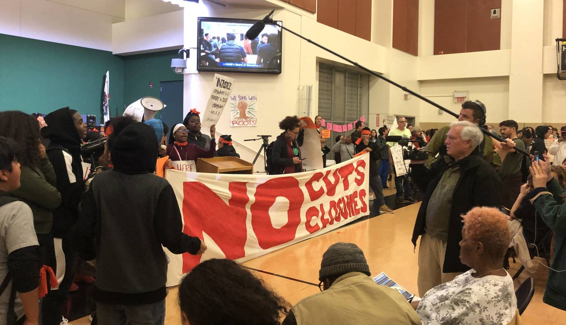Demonstrators at an OUSD board meeting on Jan. 23, 2019, at La Escuelita Elementary School voiced their opposition to the district's proposal to close Roots International Academy, a small middle school in East Oakland. Julia McEvoy/KQED