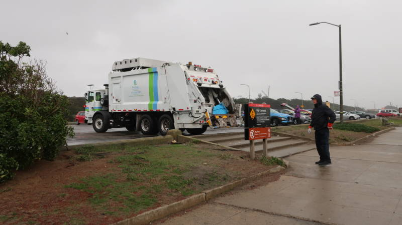A Recology truck helps haul away trash collected at Ocean Beach.