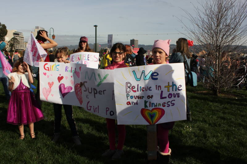 (L-R) Ashlyn Ferhart, 8; Sage White, 9; Poppy Henderson, 8; and Morgan Olsen, 9, all from West Marin, hold signs at the Oakland Women's March. The Power of Kindness sign was inspired by a song of the same name by MaMuse.