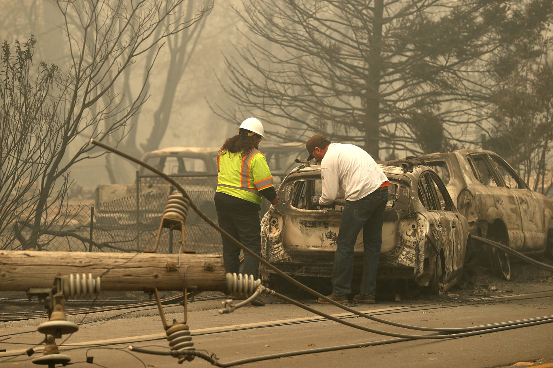 Eric England (R) looks through his friend's car that was burned by the Camp Fire on November 10, 2018, in Paradise, California. Before the filing, PG&E sought to assure the public that it would continue making safety investments in an attempt to avoid future catastrophic wildfires. Justin Sullivan/Getty Images