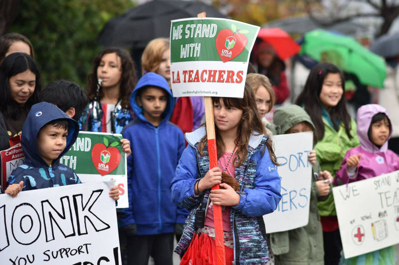 Students walk a picket line with their teachers and parents on the third day of the teachers' strike on January 16, 2019, in Los Angeles.