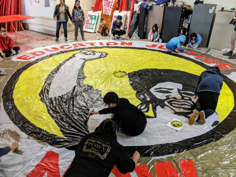 People help paint a parachute that says 'education justice now.' The image is inspired by artwork from Black Panther graphic artist Emory Douglas.