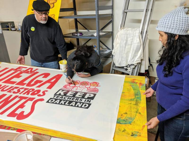 Cecilia Titizano (center) paints a sign with her husband and sixth grade daughter. 'It's inspiring. I think it's a community effort. Teachers are part of our community. They are not alone. We are here with them, and we will support them when they strike,' Titizano says.