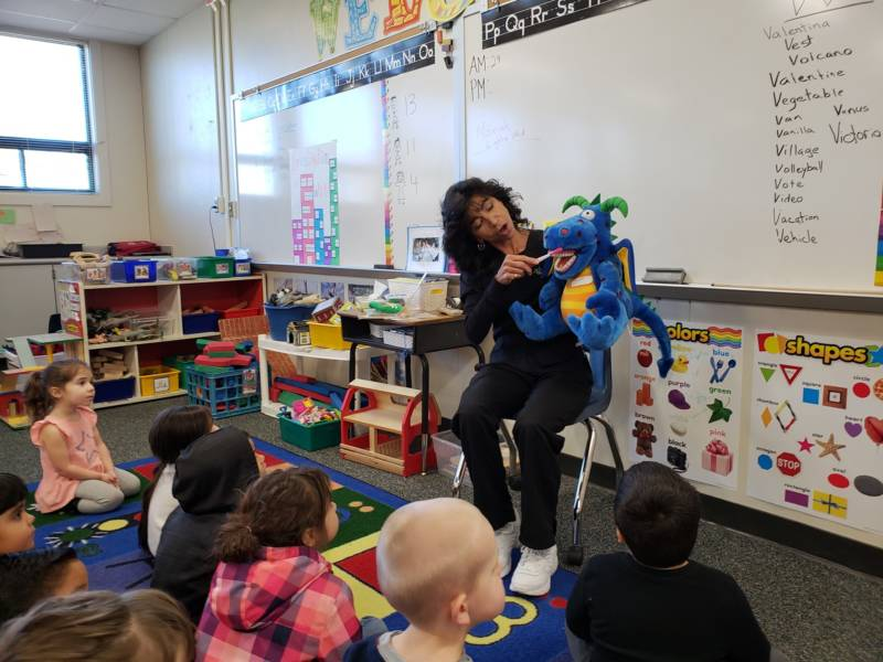 Dental hygienist Deborah Delfino shows a group of preschoolers in Lathrop, California how to brush their teeth by demonstrating with a puppet named Bob.