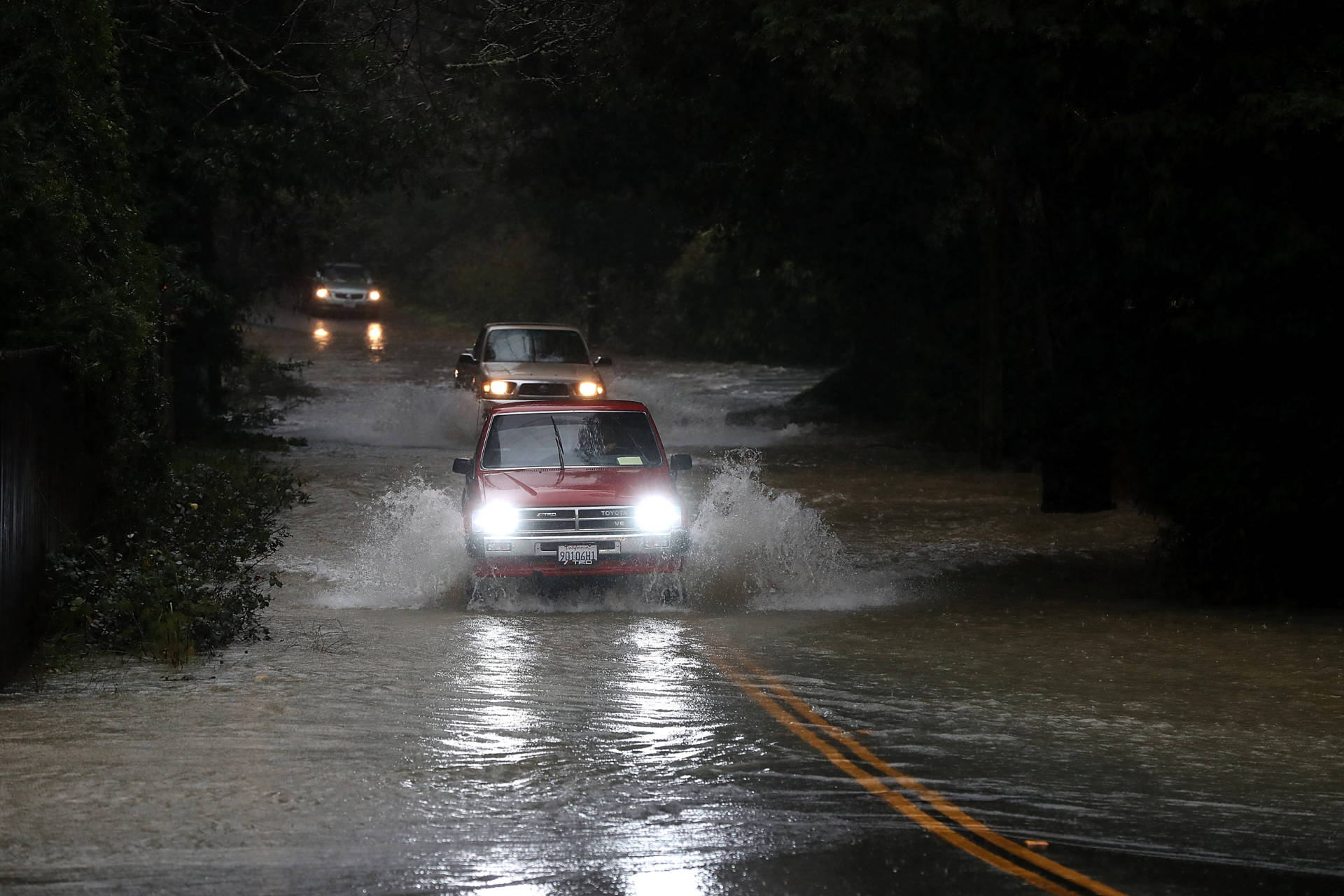 Cars drive on a flooded road in Guerneville in January 2017. The Russian River town is just downstream from Venado, a site in the northern Sonoma County hills that is one of the rainiest locations in California.  Justin Sullivan/Getty Images