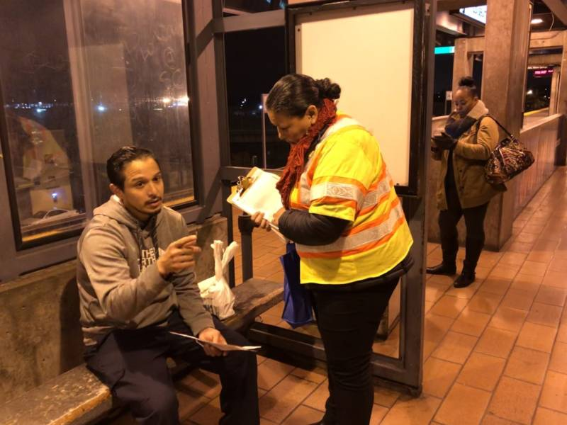 Felipe Enriquez speaks with a BART outreach staffer while waiting on platform at Coliseum station. Enriquez said BART's predawn will cost him time and money.