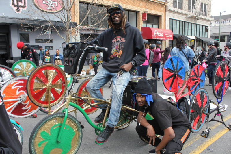 """RB"" on bike he designed and Scraper Bike team leader Chuck Davis pose at the Black Joy Parade in downtown Oakland."