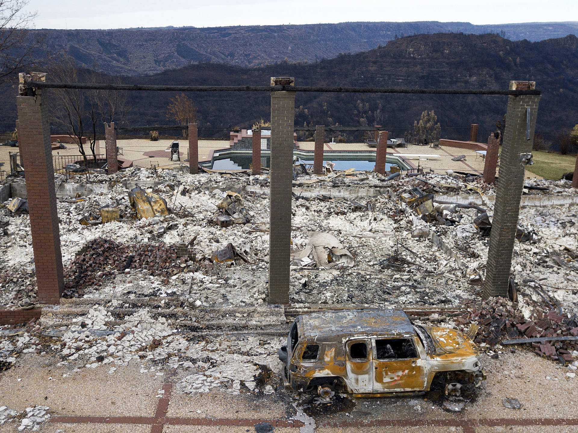 A vehicle rests in front of a home leveled by the Camp Fire in Paradise, in a photo from December. Pacific Gas & Electric has said it's 'probable' investigators will conclude its equipment ignited the November 2018 catastrophe. Noah Berger/AP