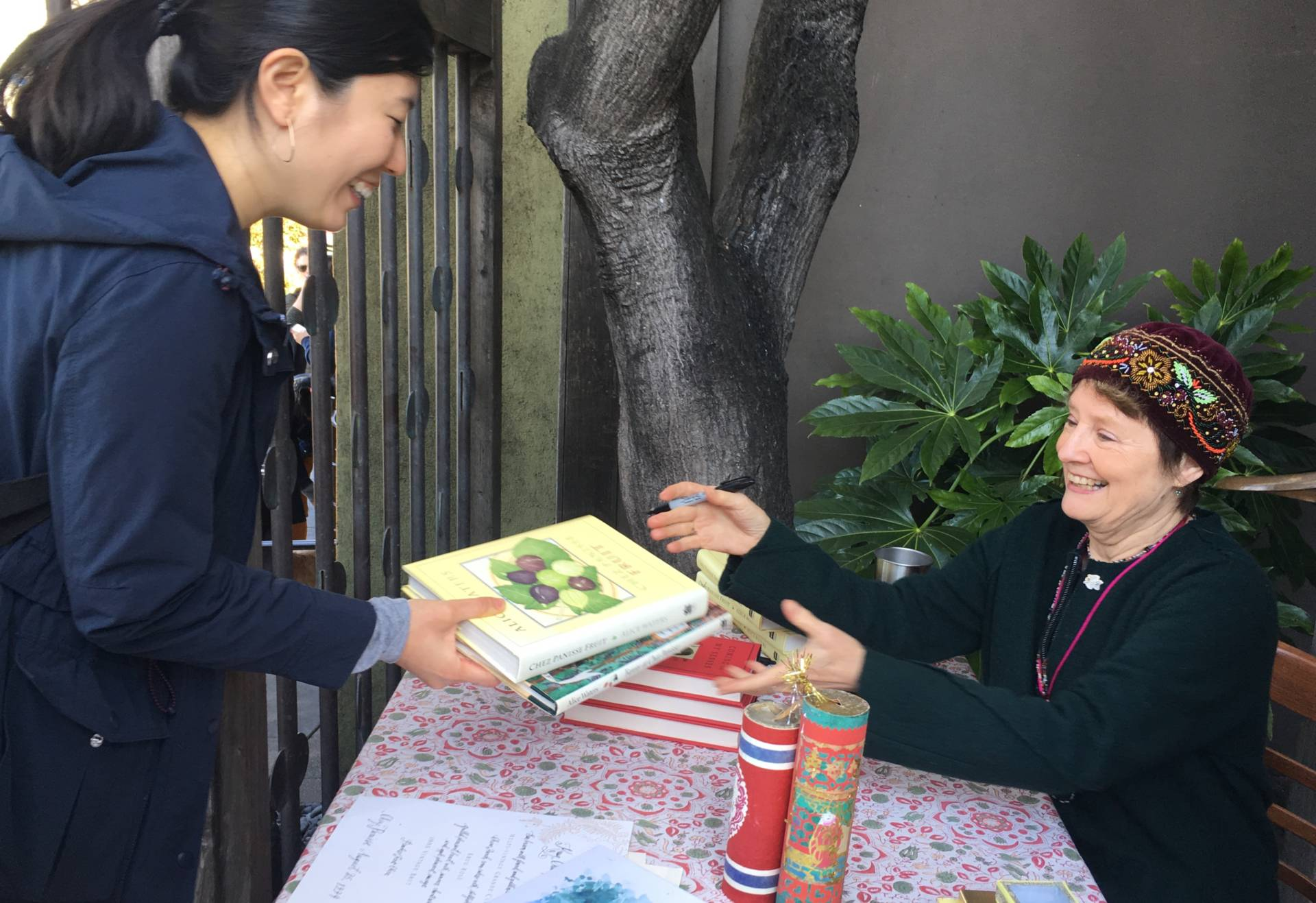 Chef Alice Waters signs books and posters outside of her restaurant. 'Always look for the flea markets, always look for the used. They can be so special because they have so many memories in them,' she says. Caroline Champlin/KQED