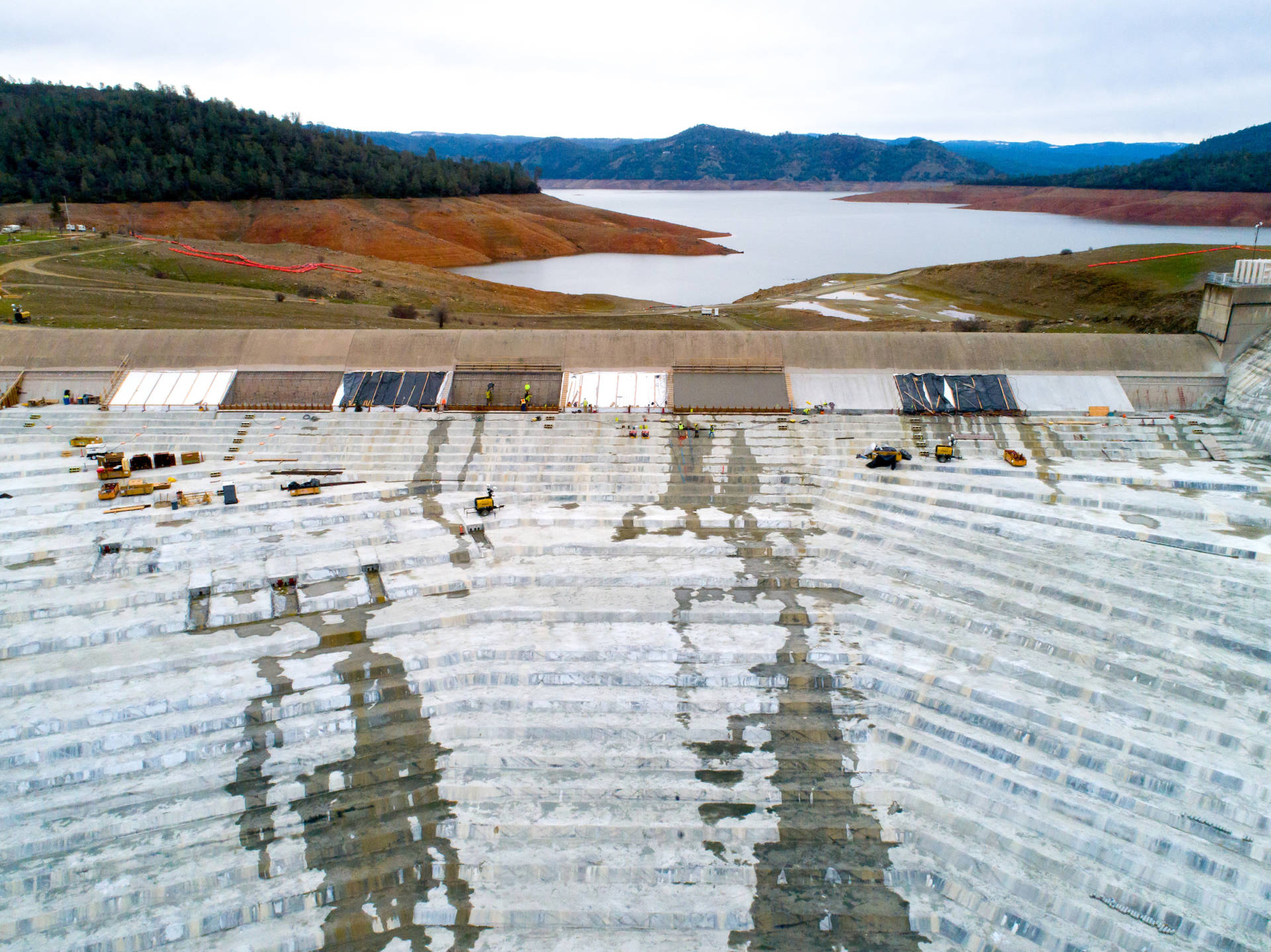 A drone provides a view of Lake Oroville and the emergency spillway splashpad as crews continue to work on the new concrete cap over the roller-compacted concrete buttress below the spillway weir. Kelly M. Grow/California Department of Water Resources