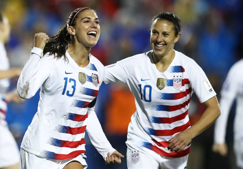 Alex Morgan #13 and Carli Lloyd #10 celebrate during the CONCACAF Women's Championship final match on Oct. 17, 2018. Morgan and Lloyd are both named as plaintiffs in the team's gender discrimination lawsuit.