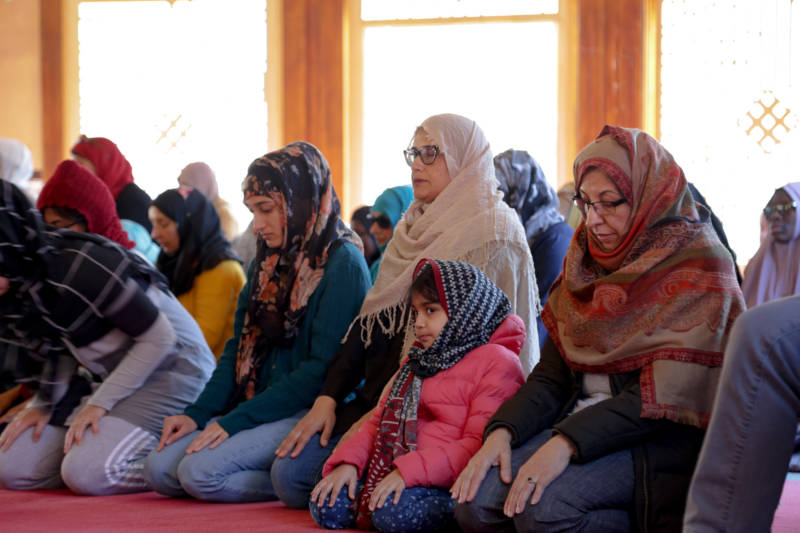 5-year-old Sophie Ahmed looks out while her mother Dr. Ruby Alvi (center in beige headscarf) is in prayer with fellow worshippers at the Islamic Society of San Francisco.