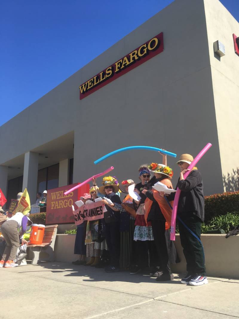 Protesters sing songs and flaunt pool toys outside of a Wells Fargo in San Carlos on March 16, 2019. They say the pool noodles represent preparation for sea level rise.
