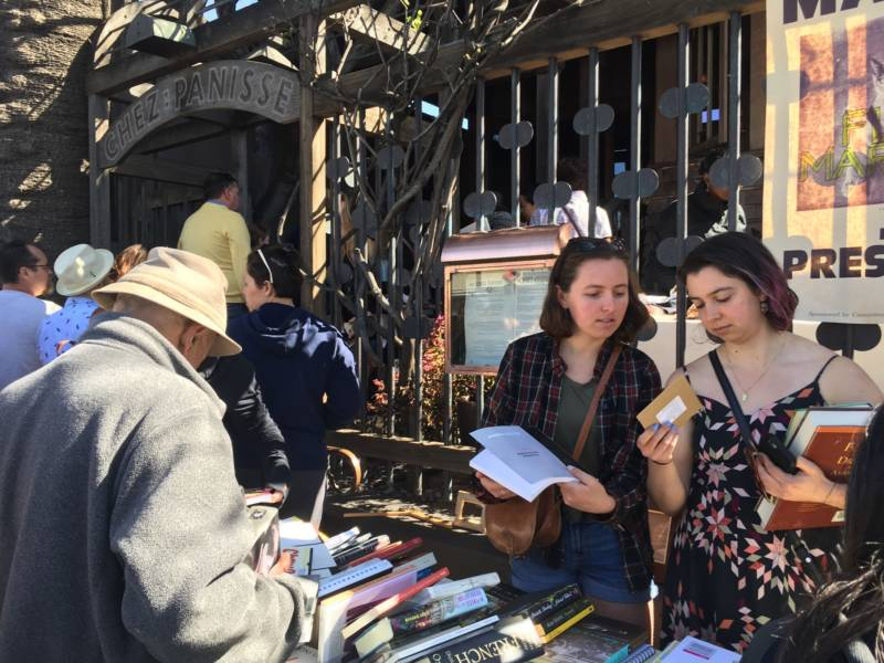 Two women browse for cookbooks and more outside Chez Panisse in North Berkeley. People came from all over the Bay Area to look through chef Alice Waters' belongings.