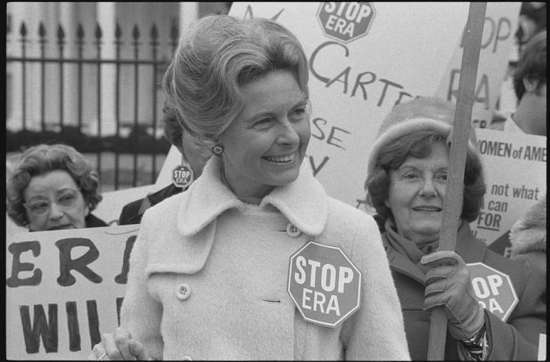 "Activist Phyllis Schlafly wearing a ""Stop ERA"" badge, demonstrating with other women against the Equal Rights Amendment in front of the White House in February 1977."