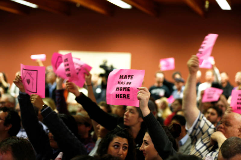 Attendees in support of the homeless navigation center hold 'Hate Has No Home Here' signs and cheer for San Francisco Mayor London Breed at a community meeting on April 3, 2019.
