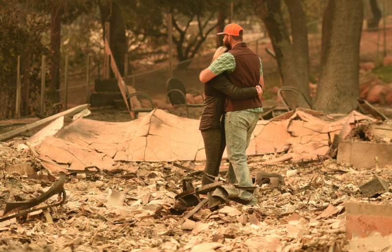 Chris and Nancy Brown embrace while looking over the remains of their burned residence after the Camp fire tore through the region in Paradise, California on November 12, 2018.