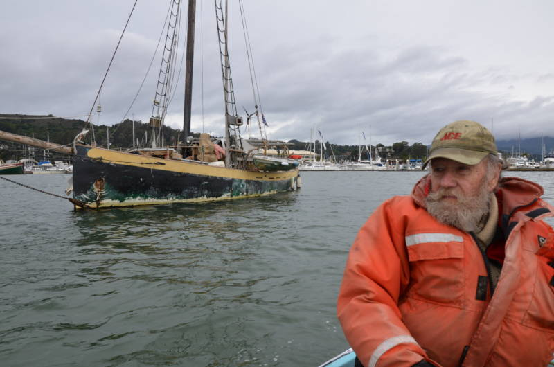 Greg Baker has had several boats since he first became an anchor-out on Richardson Bay in 1963. His current boat is anchored behind him.