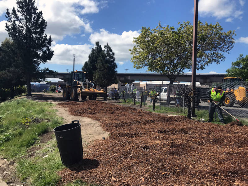 Mulch is spread over the site of the former Richmond homeless encampment on April 16, 2019.
