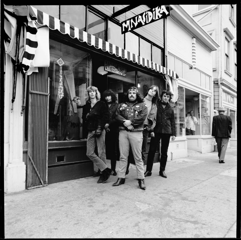 Members of the Grateful Dead stand outside Mnasidika in the Haight-Ashbury neighborhood. Mnasidika was an influential hippie boutique and meeting place in the 1960s.