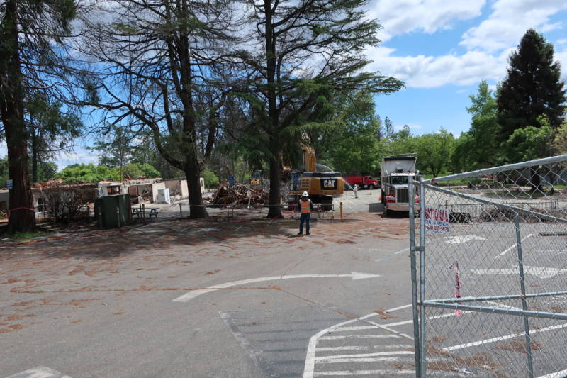 Workers with a backhoe remove debris from the burned down Paradise Elementary.