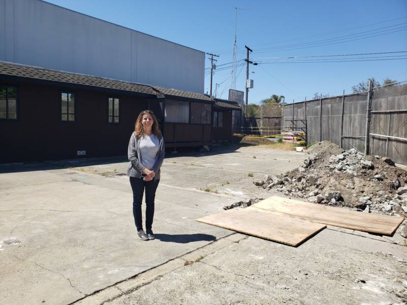 Mission Kids Co-Director Christina Maluenda Marchiel stands on the site of the school's future location.