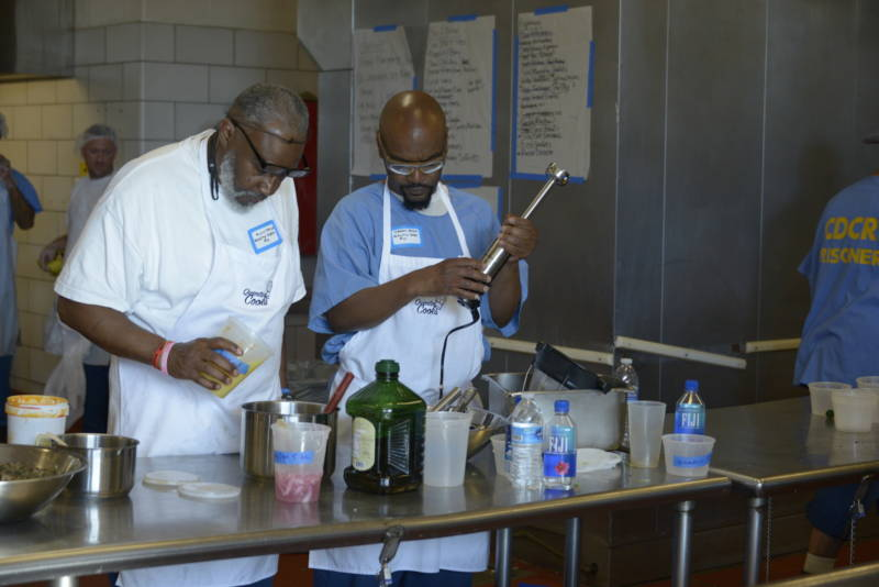 Alvis Taylor (left) and Derry Brown, both inmates at San Quentin, prepare food for the fifth Quentin Cooks graduation dinner at San Quentin State Prison on May 22, 2019.
