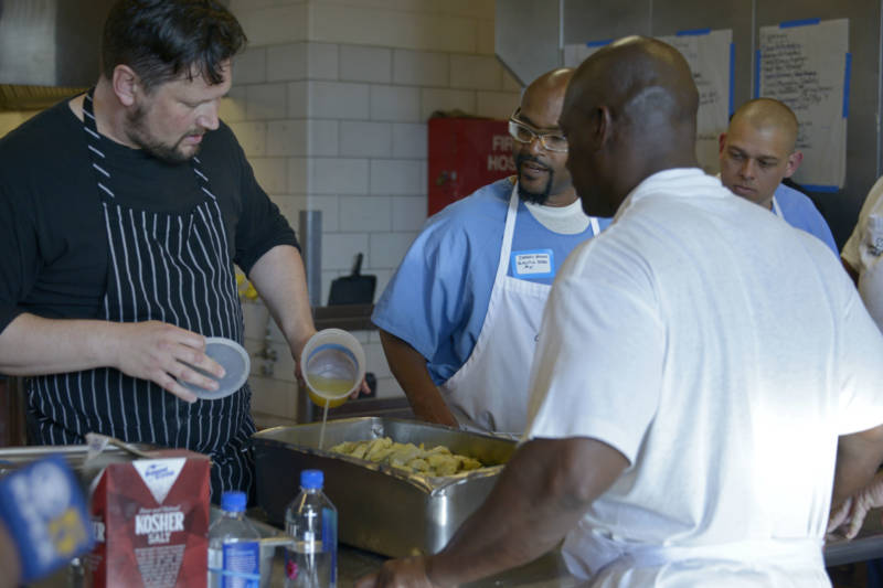 Chef Huw Taylor (left) helps students prepare food for the fifth Quentin Cooks graduation dinner at San Quentin State Prison on May 22, 2019.