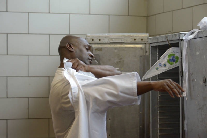 Ron Simmons puts on his chef's coat before the fifth graduation dinner of Quentin Cooks at San Quentin State Prison on May 22, 2019.