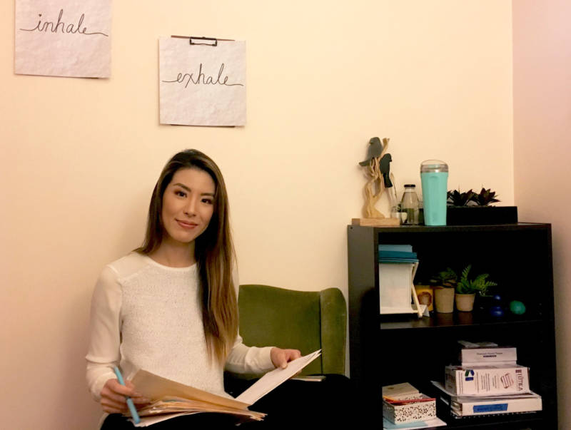 Sophia Ng reviews some paperwork in an office at Lowell High School's Wellness Center. As a mental health therapist, Ng visited schools in San Francisco and counseled students.