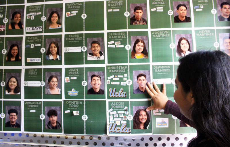 Dafne looks at a wall with images of classmates who've been admitted to college on May 23, 2019.