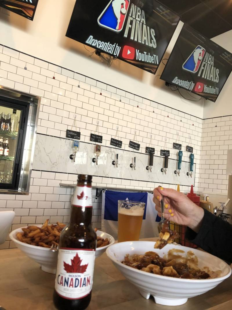 A patron of Augie's Montreal Deli drank Canadian beer and ate poutine for Game 2 of the Warriors-Raptors series on Sunday.