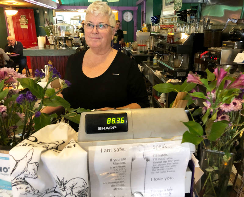 Mary Pulskamp wears a safety pin on her shirt while working the register at Rosebud's Cafe. The signs below signify that the cafe is a safe space for those who feel persecuted.