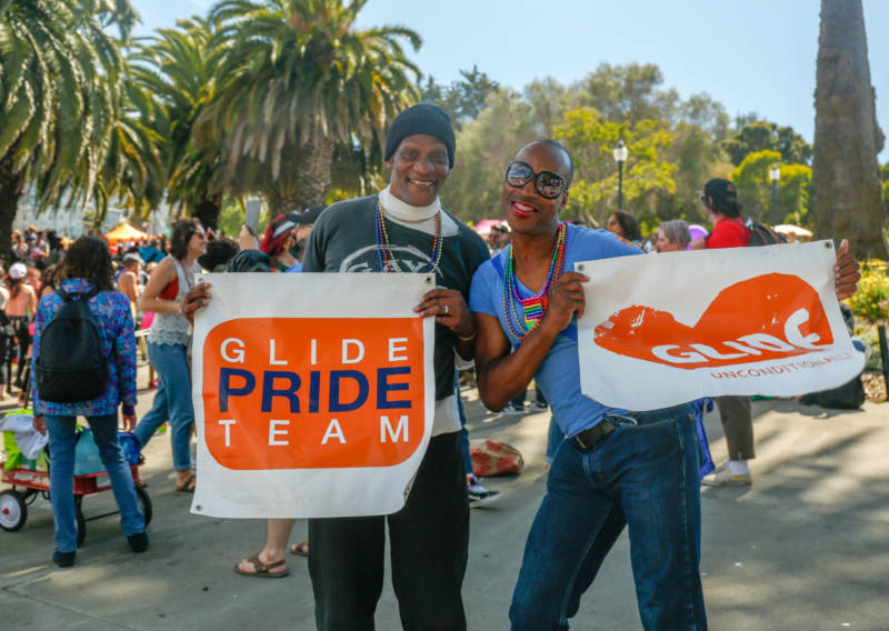 "Two men hols banners that say ""Glide Pride Team."""