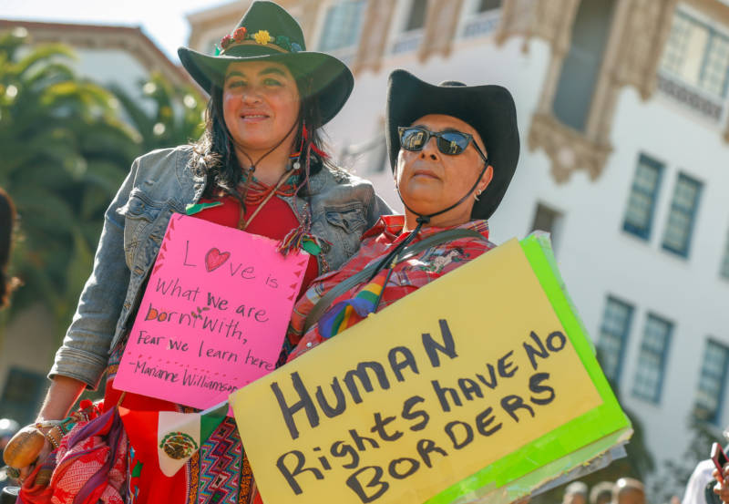"Partners Victoria Miycue and DC Alcalá wear black cowboy hats, hold a small Mexican flag and a yellow sign that say ""Human Rights Have No Borders."""
