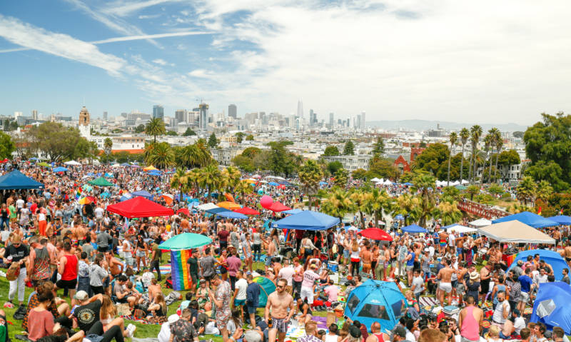 Thousands of people gather at Dolores Park on a beautiful sunny day. Picture looks like something out of a movie.