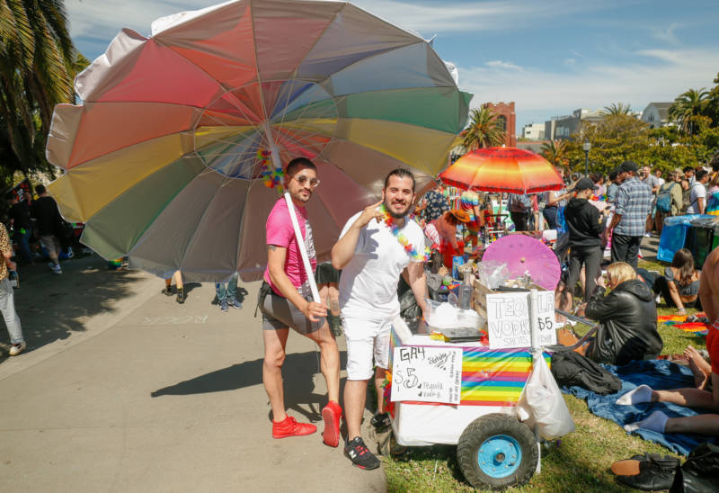 A man waves a huge rainbow umbrella next to an ice cream cart.