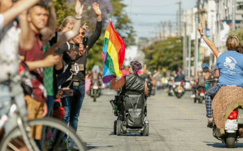 A person rolls down the parade in their electric wheelchair.