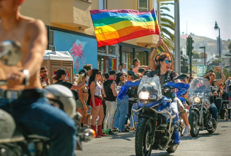 A person on a motorcycle waves a rainbow flag.