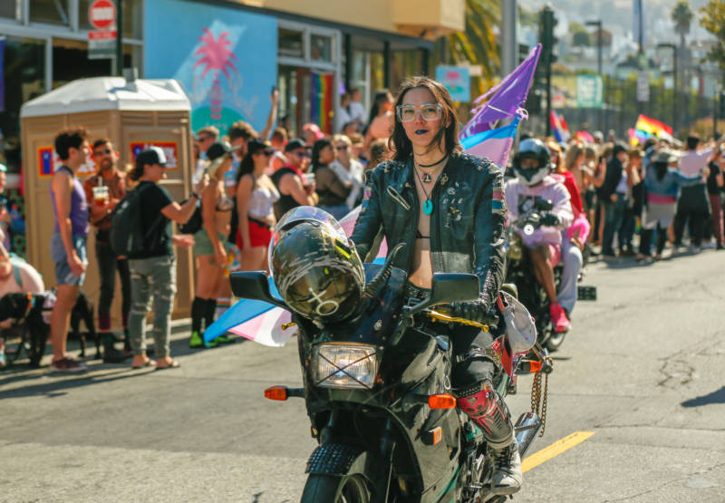 A woman with long hair, wearing a black leather jacket and a bikini top rides her motorcycle down the march.