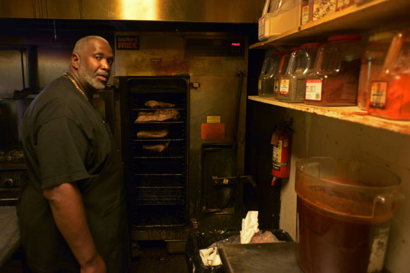 Joel McCarter, a graduate of the Quentin Cooks program at San Quentin State Prison, now works at Smoke Berkeley. He is seen standing in front of the restaurant's large smoker preparing the next day's brisket on May 28, 2019, in Berkeley.