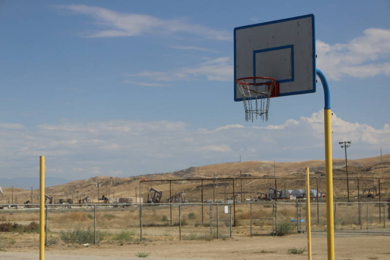 Oil pumping units as seen from the basketball court at McKittrick Elementary School.