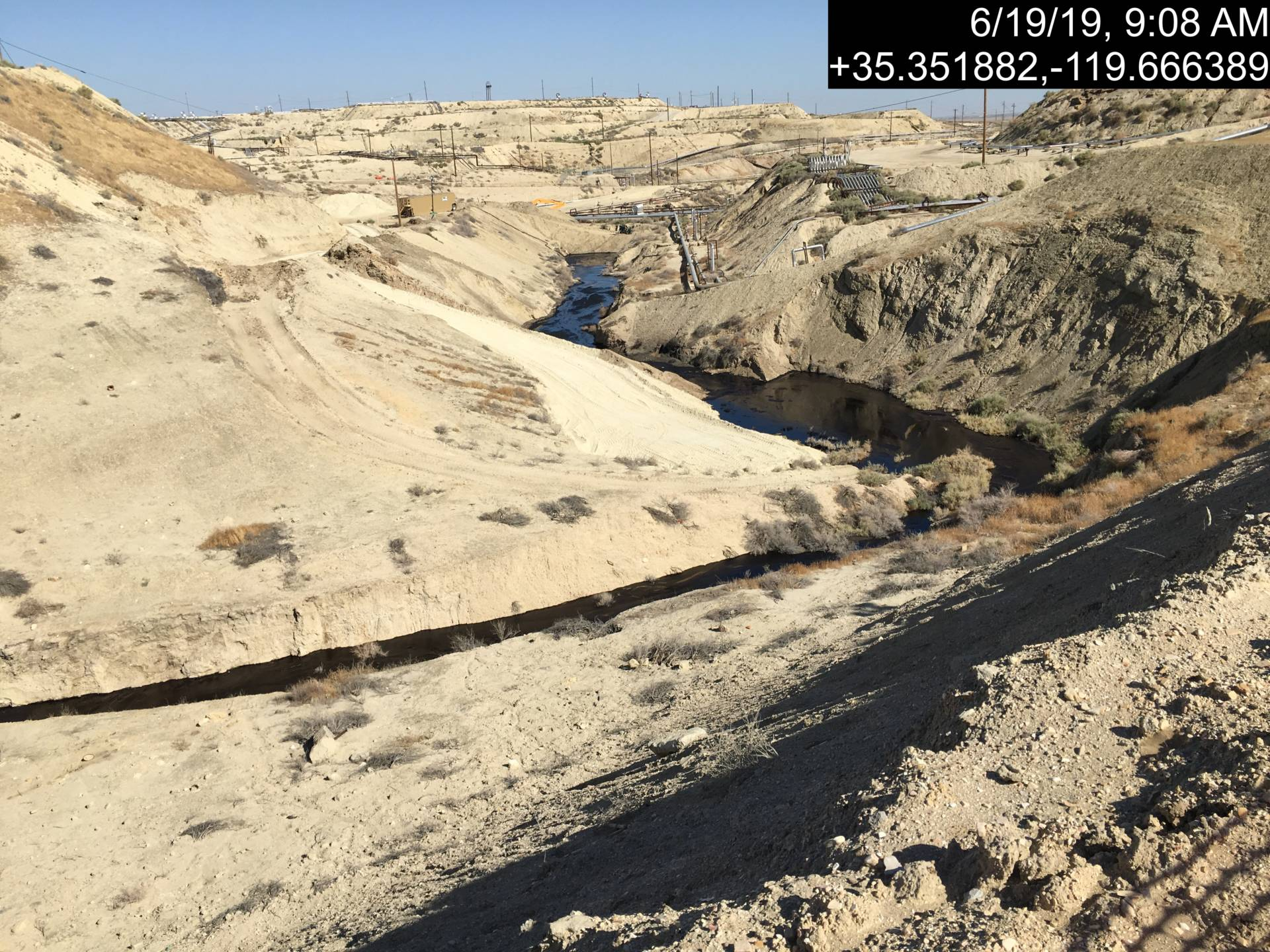Image showing portion of dry creekbed fouled by oil spill at a Chevron well site in Kern County.  California Department of Conservation