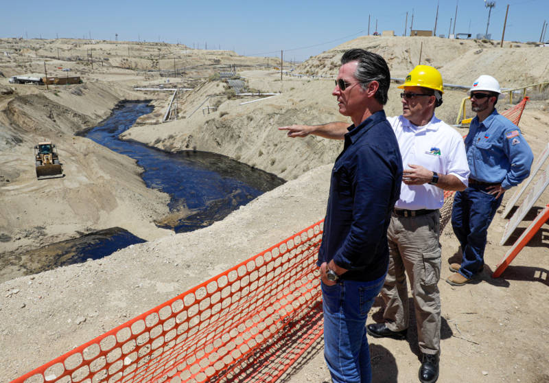 Gov. Gavin Newsom is briefed by Billy Lacobie, of Chevron (right), and Jason Marshall (center), acting supervisor of the state Division of Oil, Gas and Geothermal Resources (DOGGR) on Wednesday while touring the Chevron oil field near Bakersfield where a spill of at least 974,400 gallons of fluid have flowed into a dry creek bed.