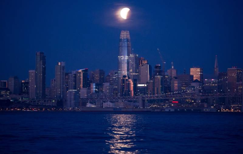 A super blue blood moon is seen during a partial lunar eclipse over Salesforce Tower in San Francisco, California before dawn on January 31, 2018.