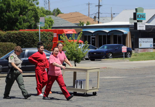 Immigrant detainees help a sheriff's deputy carry items to a truck outside of the Yuba County Jail.